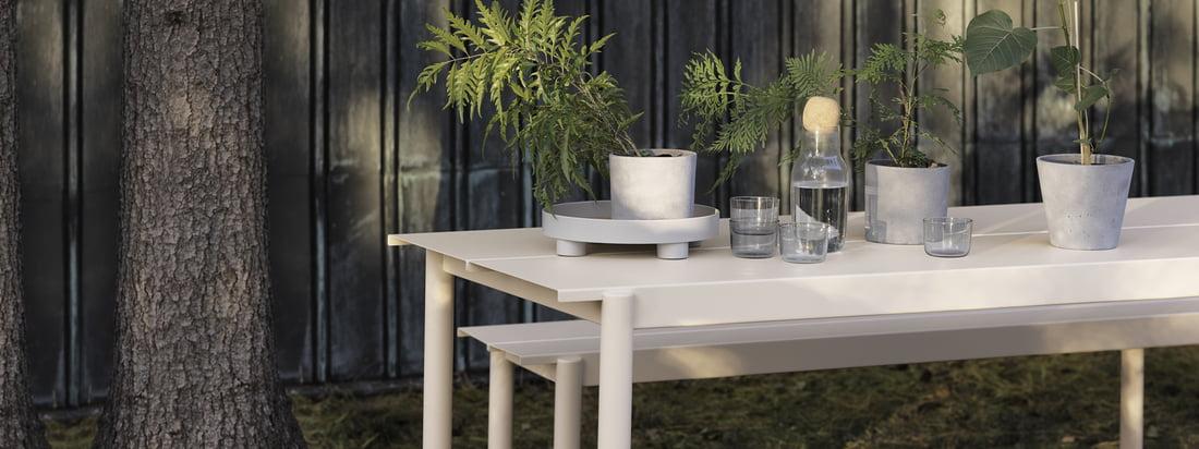 Lineaire stalen bank en tafel in wit van Muuto in de ambiance van Muuto. Tafel en bank kunnen door hun stalen constructie perfect gebruikt worden in de tuin en inspireren door hun moderne design.