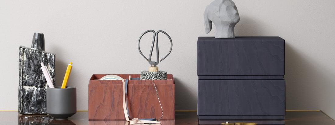 De opbergdozen van applicata op het bureau. Praktische gebruiksvoorwerpen zoals een schaar of garen kunnen veilig en discreet worden opgeborgen in de dozen.