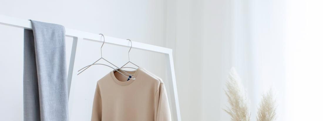 De combinatie van een witte kleerkast, zwarte metalen kleerhangers en een klein houten bankje heeft een Scandinavische eenvoud. 3 must-haves voor een succesvolle kleedkamer.
