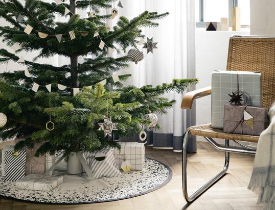 De geest van Kerstmis is hier met de messing ornamenten, kerstboomstandaard en kerstboomdeken van ferm Living